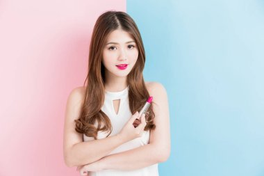 A beautiful girl  holding red lipstick isolated on pink and blue background.