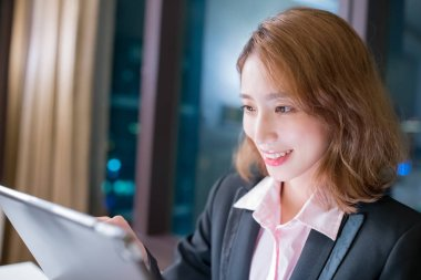 business woman smile happily and use digital tablet work at night