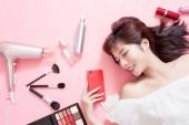 junge schöne Frau hält Smartphone in der Hand und genießt mit ihren Kosmetikutensilien - sie liegt auf dem rosafarbenen Boden