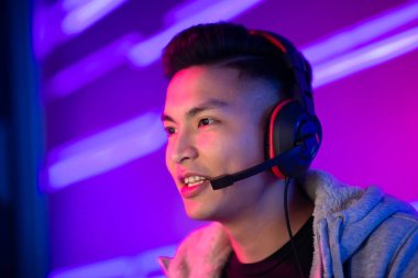 Young Asian Handsome Pro Gamer having live stream and playing in Online Video Game