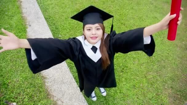 Lány gratuate felvonó karját boldogan