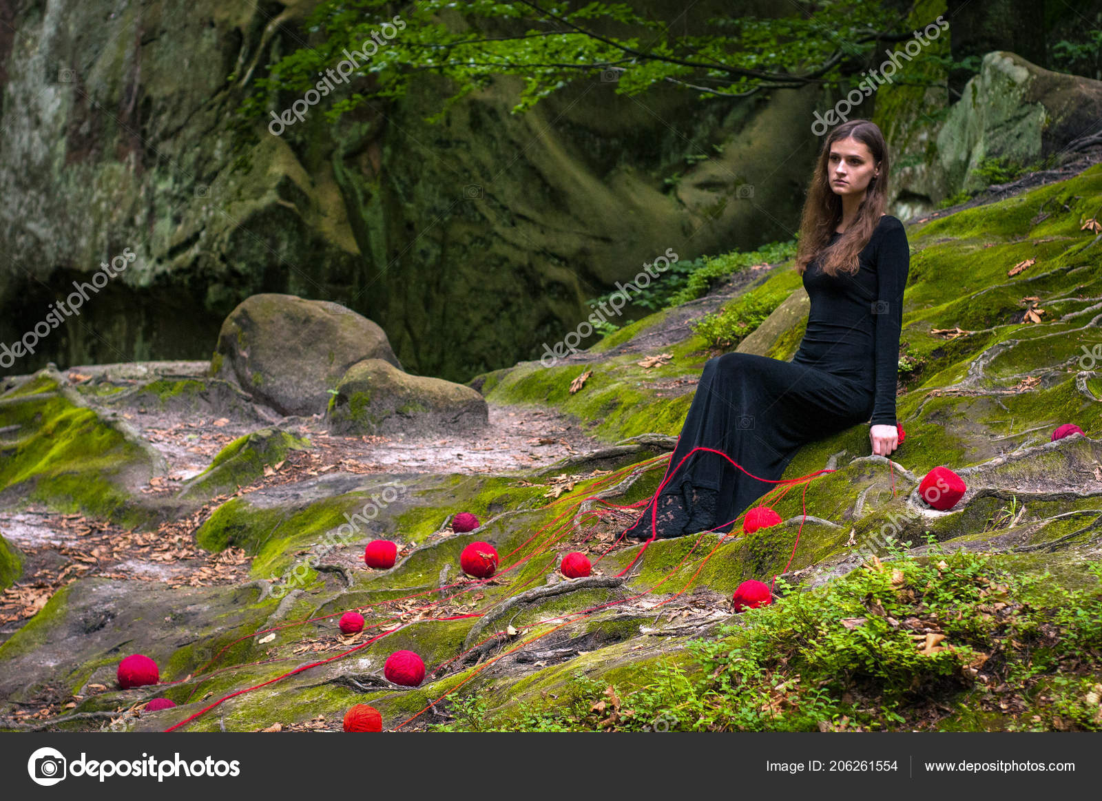 Alone beautiful girl is sitting on green moss in a fairy forest portrait of a brunette in a black dress that lies on the green moss and around scattered
