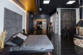 sötét modern stílusos férfi apartman belső világítással, dekoratív falak, kandalló, öltözködési terület és hatalmas ablak
