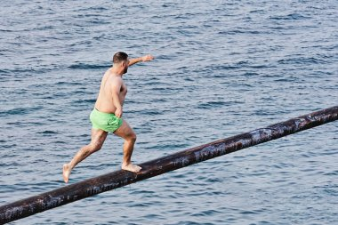 Competitor tries to grab flag on Gostra on wooden pole covered in grease and fat