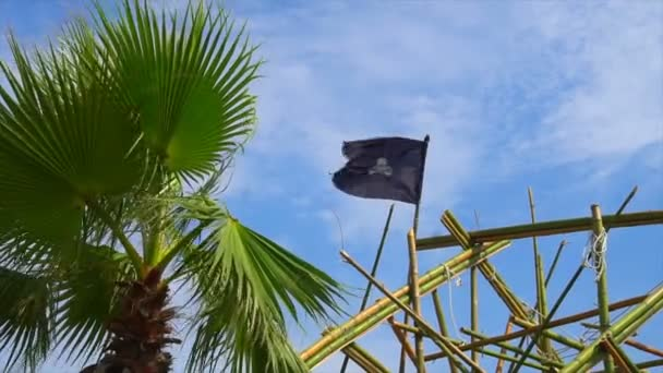 Torn tattered pirate flag waves in the wind tied to rigging on tall ship Dewarcuci as clouds pass with blue sky
