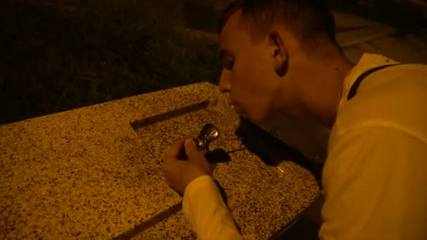 a young guy drinks water from a fountain in the evening