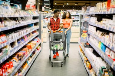 Family shopping for groceries in supermarket. Smiling african american couple with shopping trolley choosing food in supermarket