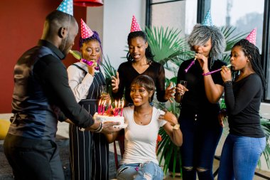 African Teenagers with party horns and a cake celebrating a birthday