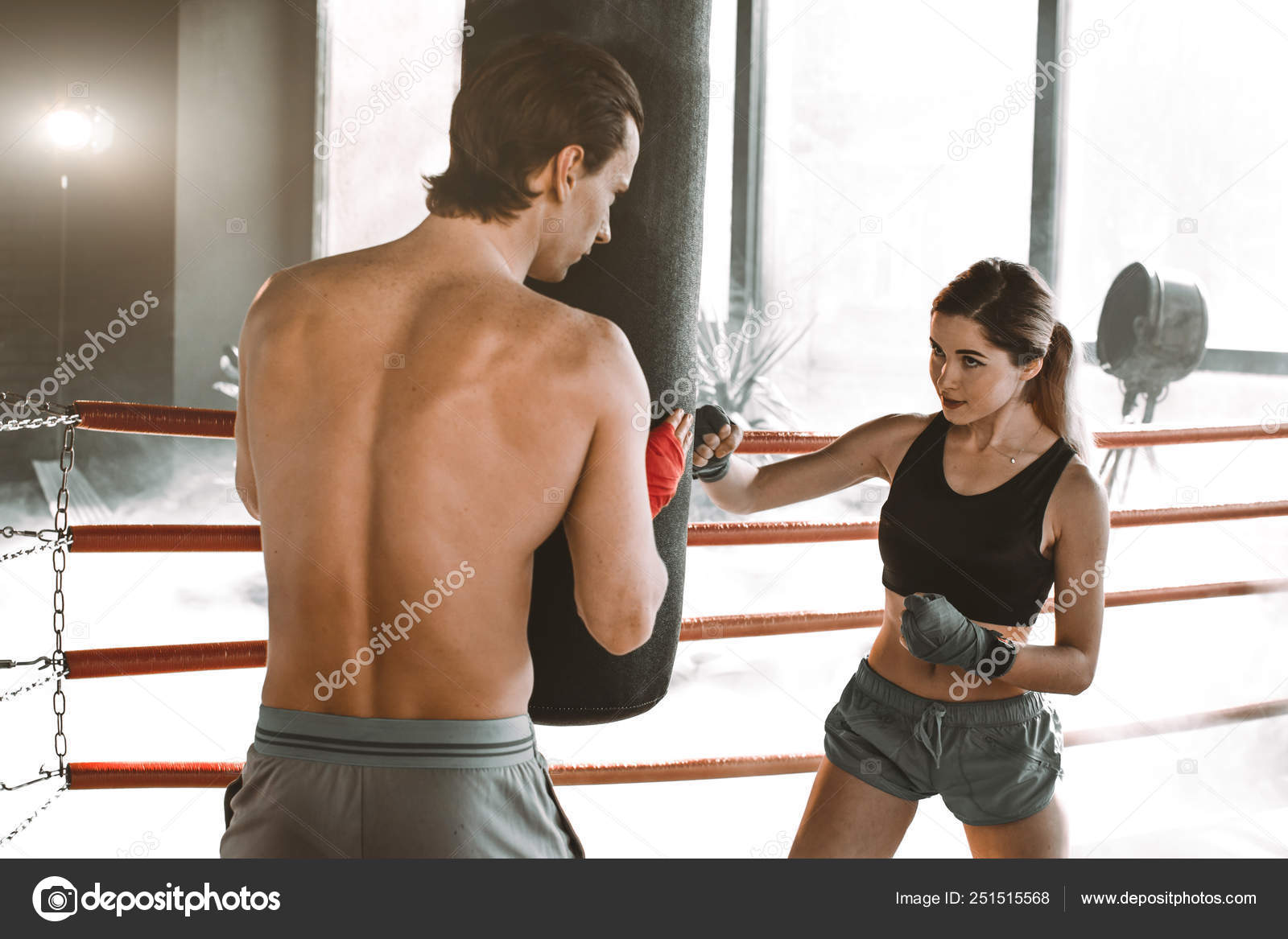 Trainer teaching a girl how to hit punches  Girl wearing boxing