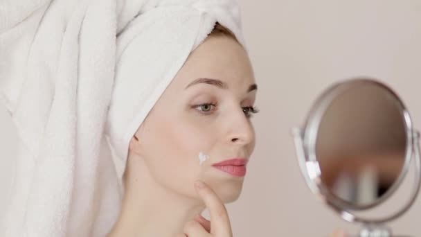 Portrait of happy smiling beautiful young woman with white towel on her head, touching problem skin areas and applying cream, isolated over white background