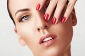 Krása žena tvář portrét. Krásný model Spa dívka s dokonalou čerstvé čisté kůže a červená manikúra. Mládí a koncept péče o pleť