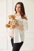 Pregnant Woman in white shirt holding teddy bear. Pregnant beauty young mother portrait, caressing her belly and smiling. Healthy Pregnancy concept, brunette expectant female.