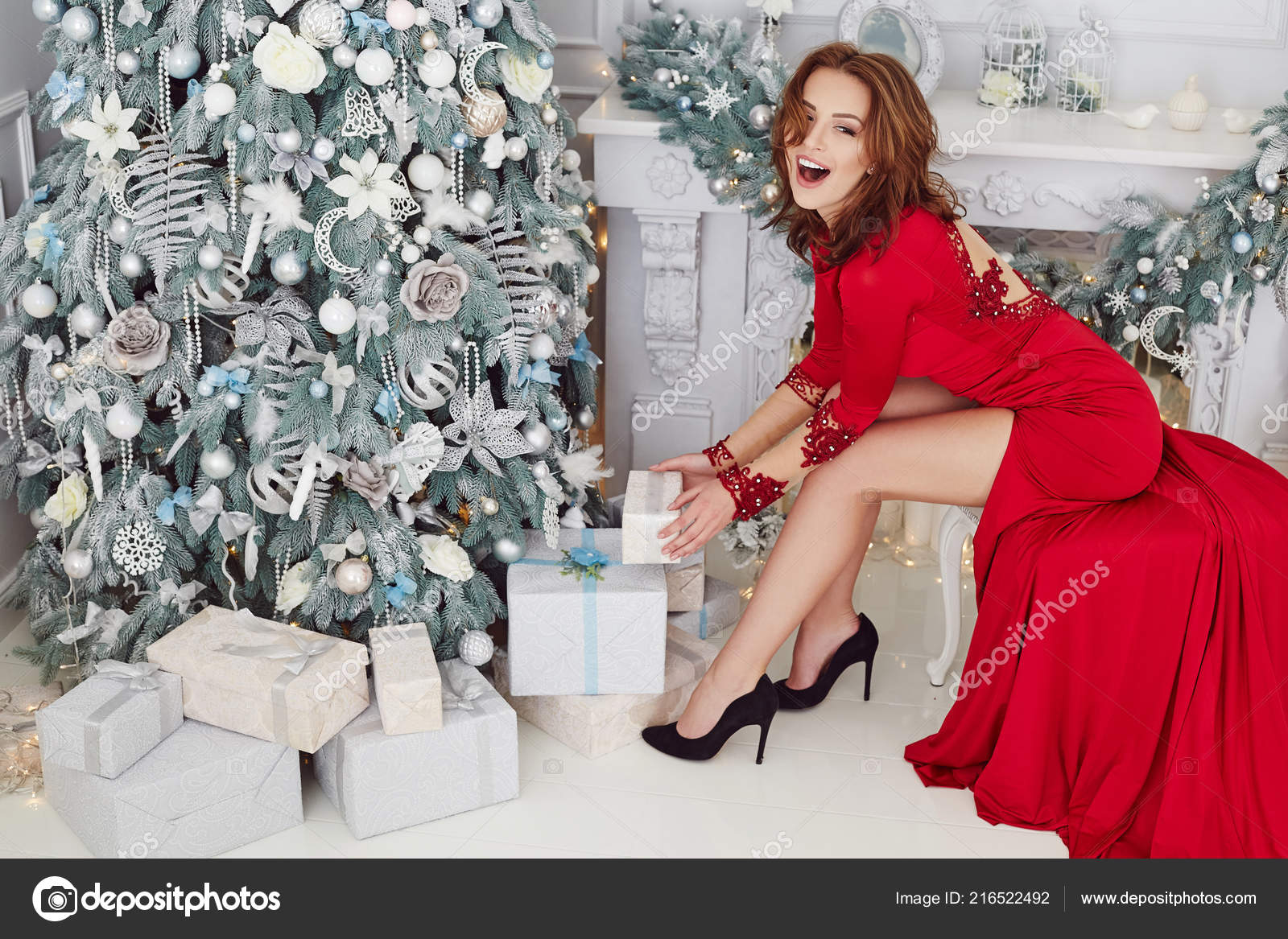 gorgeous glamour women in a long red evening dress sitting in a chair near the decorative fire place beautiful new year and christmas scene beauty fashion