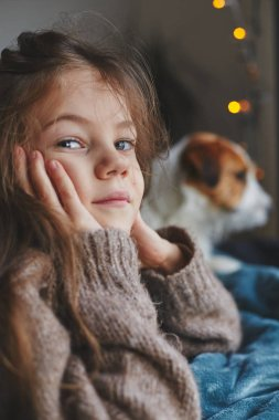 Portrait of a cute little smiling girl with jack russell terrier puppy behind. Cold autumn or winter, cozy weekend at home