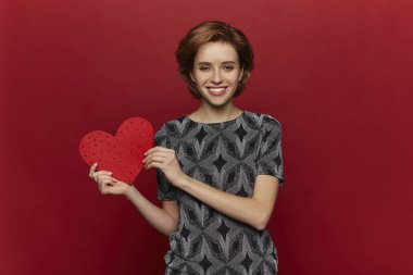 Beauty cheerful Young fashion model Girl with big Valentine Heart in hands. Love. Beautiful young woman in dress. Valentines Day advertising. Red background. - Image