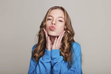 Close up photo of pretty cheer nice cute attractive teenage girl sending air kisses wearing bluer pullover isolated on grey background