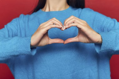 Woman making heart on chest isolated on red background, studio shoot, valentine's day love concept