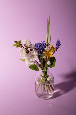 Beautiful fresh flowers in glass vase, soft home decor on pink background.