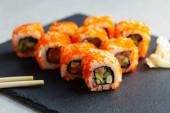Sushi-Rollen mit Stäbchen. Japanisches Essen. California Sushi Roll Set mit Lachs, Gemüse und Kaviar in Nahaufnahme. Speisekarte japanischer Restaurants