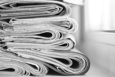 News - Folded newspapers stacked in row, selective focus on papers with blurred background. Paper texture