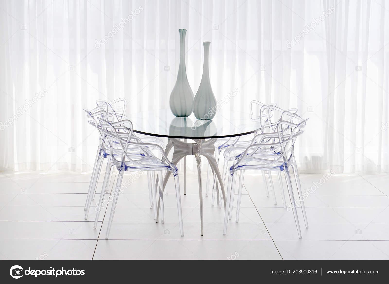 Grande tavolo vetro con sedie plastica vasi vetro nel salotto