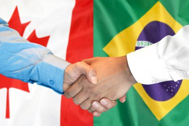 handshake on Brazil and Canada flag background.