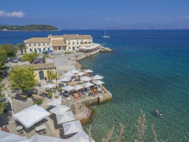 Corfu, Greece - June 7, 2017: Faliraki beach Alecos Baths - one of the oldest public bathing spots, with the En plo restaurant in Corfu Town, turquoise blue water of the Ionian Sea