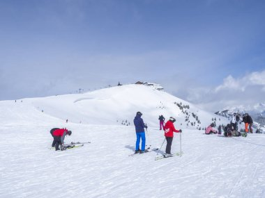 Zell Am See, AUSTRIA, March 14, 2019: Skiers on the top of Smittenhohe mountain at Kaprun ski area preparing to go down into the valley and takeing pictures selfies. Blue sky sunny winter day. stock vector