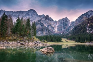 Beautiful sunset landscape of Lago or Laghi di Fusine lake in Italy with spruces on shore on blue sky and mountains background