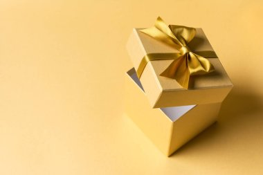 Beautiful golden square gift box with shiny satin bow for christmas or birthday presents on gold background with copy space