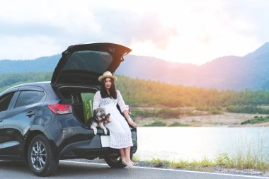Happy young woman traveler sitting in hatchback car with dogs while parking near lake with mountain view and sunset. Cheerful female in white dress travels with pets in summer vacation in road trips.