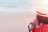 Fotografia Rear view of young worried woman traveler in hat sitting on beach chair and hand holding smartphone while relaxing on tropical beach and sunset sea background. Summer vacation, travel and relaxation.
