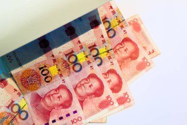 Counterfeit dollar currency detection, Checking one hundred chinese yuan banknotes with ultraviolet light or black light machine on white background.