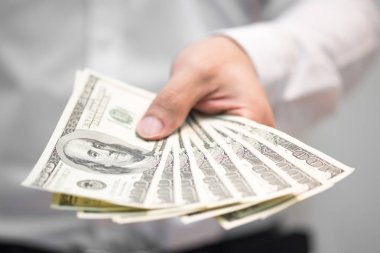 Businessman holding money on hand, Spreading one hundred US Dollar bills in financial concepts, Selective focus.