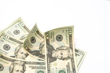 Stack of twenty dollar bills on white table background.