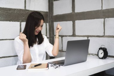 Happy successful young asian woman celebrate while working with laptop at home. Euphoric and excited college girl raising arms after get good news. Education, Technology and startup business.