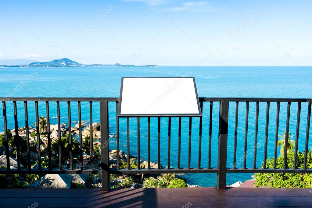 Blank advertising billboard on steel fence over calm blue sea and sky background at tropical island. Outdoor sign panel can advertisement for display, guide map, food menu and travel information.