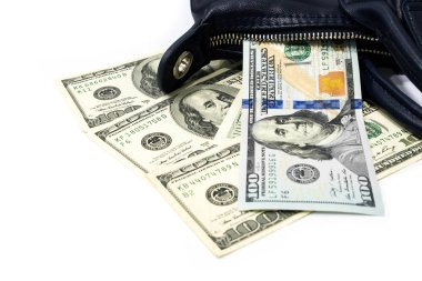 One hundred dollar bills fell out of dark blue ladies handbag on grey background in lavish spending money  concept.