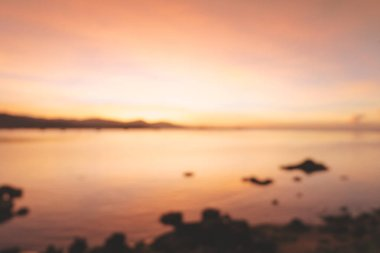 Blurred of beautiful blazing sunset landscape at black sea and mountain above orange sky with awesome sun golden reflection on calm sea as a background. Amazing summer sunset view on the beach.