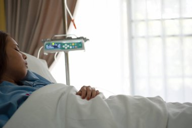 Close up asian woman patient sleeping in white blanket lying on bed with saline solution intravenous drip (iv) in hospital VIP room. Recovering after surgery. Healthcare and medical concept.