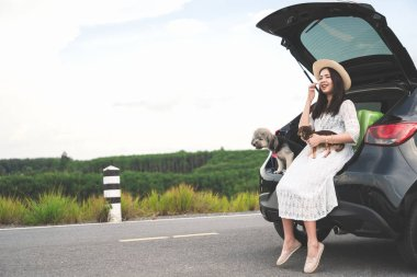 Happy young woman traveler sitting in hatchback car with dogs on road and sunset sky. Cheerful female in white dress travels with pets in summer vacation in road trips. Lifestyle, outdoor, friendship