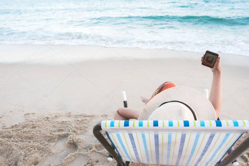Rear view of Happy woman in hat sitting on beach chair taking photo herself and enjoy vacation on tropical beach. Female traveler selfie post social media at summer sea. Lifestyle, internet concept.