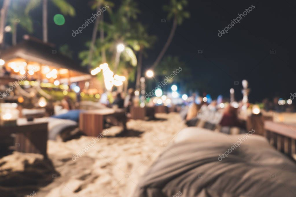 Blurred background of beach bar and restaurant view at night in summer vacation. Defocused and bokeh of seat cushion and table on beach for night life party with cocktails and music entertainment.