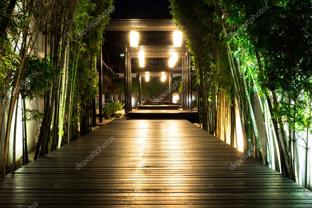 Soft focus of black wooden garden path with bamboo on both side at night, Garden decorative lighting.