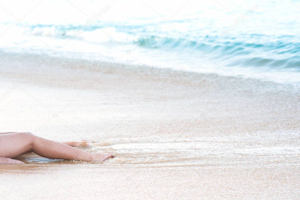 Woman legs relaxing lying down on white sand beach and tropical sea waves hitting shore in summer vacation. Outdoor travel, holiday and relaxation concept.