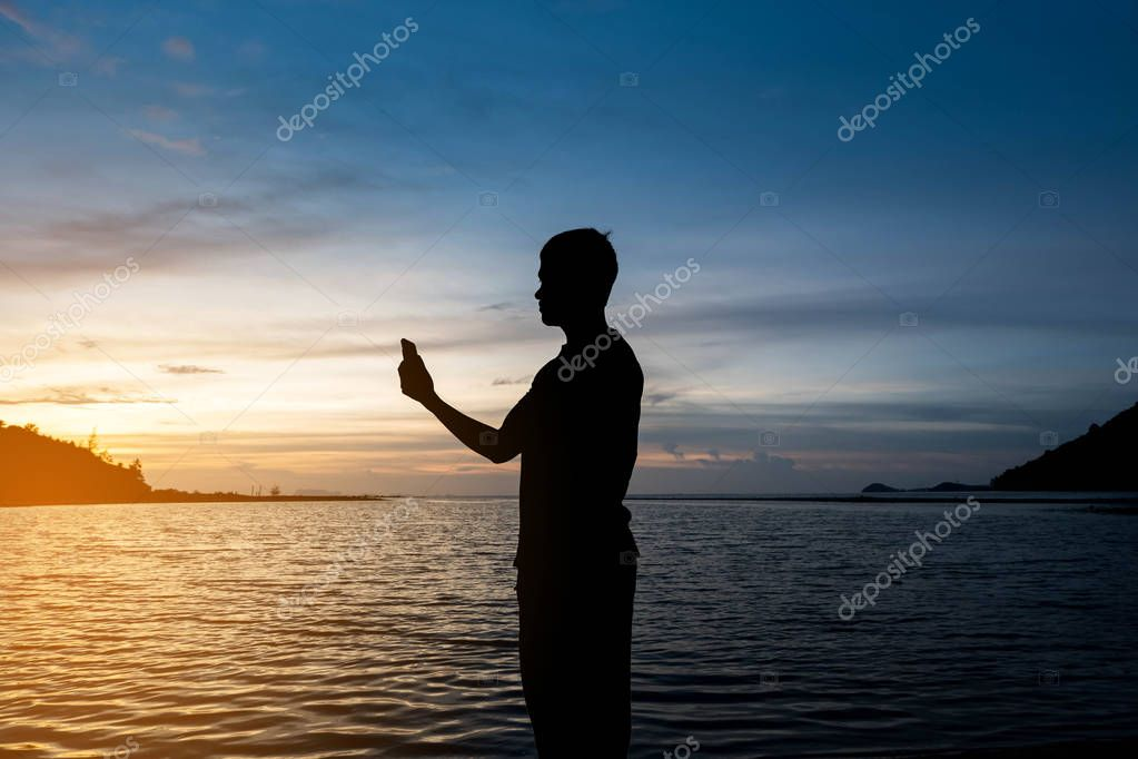 Silhouette of man standing alone on tropical beach with calm blue sea and holding smartphone at beautiful twilight sunset. Lonely man concept.