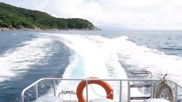 Speedboot, das sich mit voller Fahrt auf tiefblauem Meer mit Rettungsring bewegt, hängt am Heck des Bootes über dem Sommerhimmel mit Wasserschaum und Wasseroberfläche dahinter. Motorboot bewegt sich auf dem Meer.