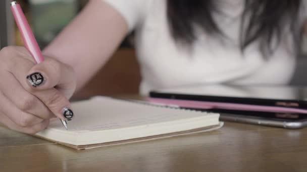 Detailní záběr žena ruku psaní její myšlenky a obsahu na zápisník s perem na dřevěný stůl s tablet, smartphone v kavárně.