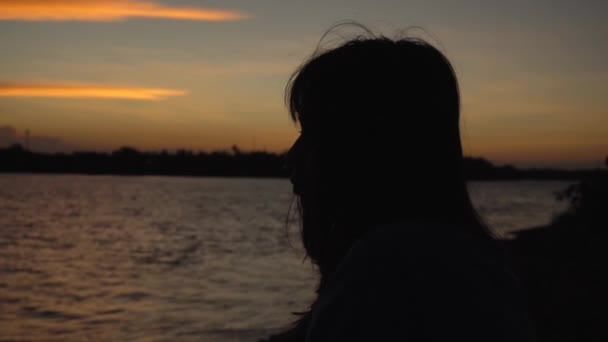 Silhouette of young asian lonely woman looking at lake view at sunset thinking about life, slow motion panning shot. Girl sitting beside river relaxing and enjoying evening peace and calm summer.