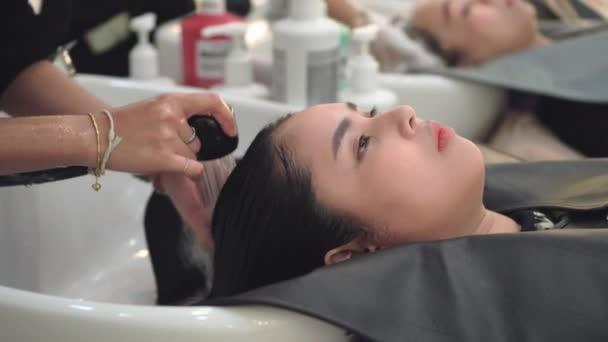 Šťastná mladá asijská žena kadeřnictví praní a masírování vlasů v salonu krásy. Mladá žena v obchodě vlasy. Vlasy spa a léčba, krásy a lidé koncepce.